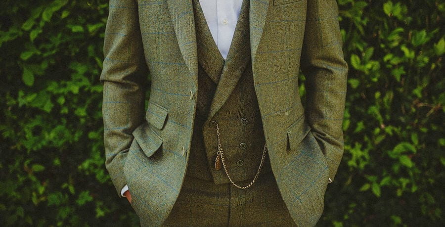 The groom stands in front of a large bush dressed in a green tweed suit with an old watch hanging from his waistcoat