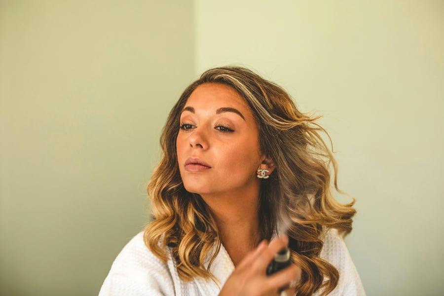 The bride sprays hairspray onto her hair
