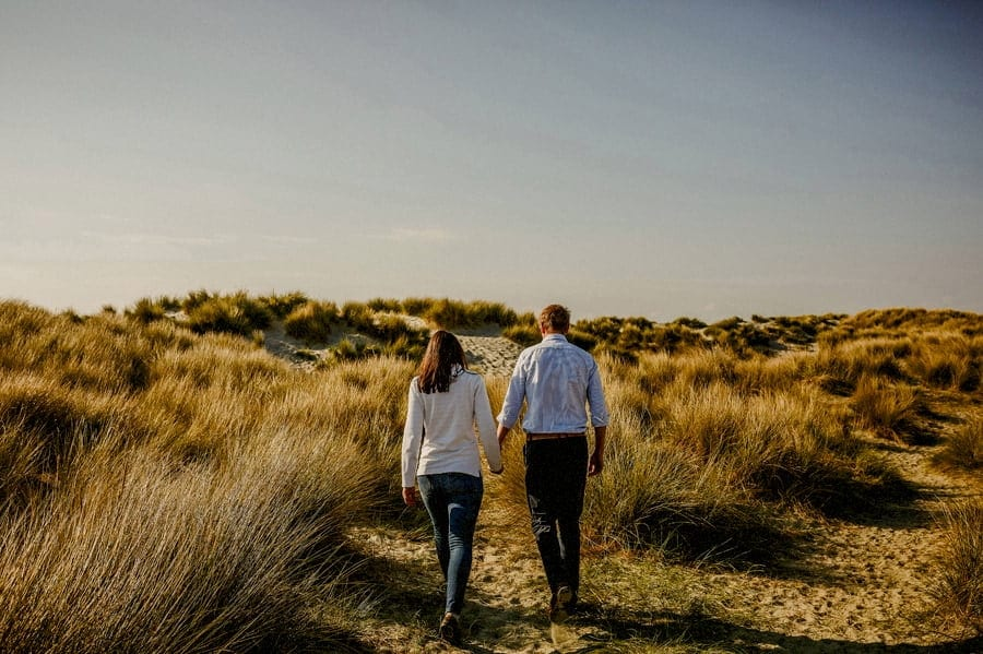 A man and lady hold each others hand and walk side by side along the sand dunes at West Wittering beach