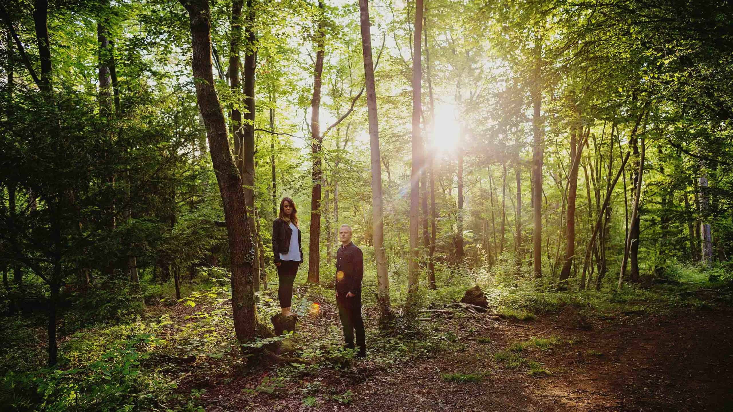 A man and lady stand next to each other and pose for a photograph in woods