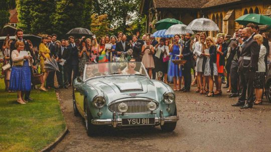 The bride and groom leave the church in a vintage car as the wedding party watch behind them
