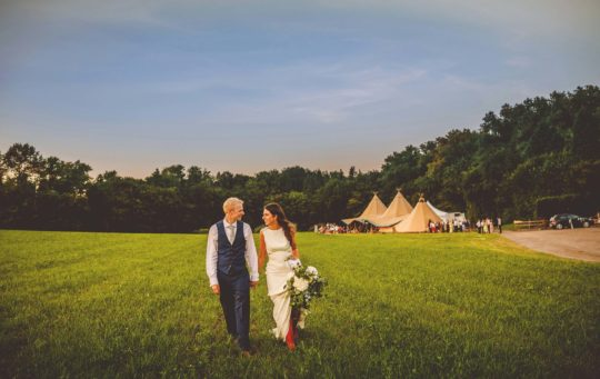 A bride and groom walk across the field away from the tipi at the Yurt retreat in Somerset